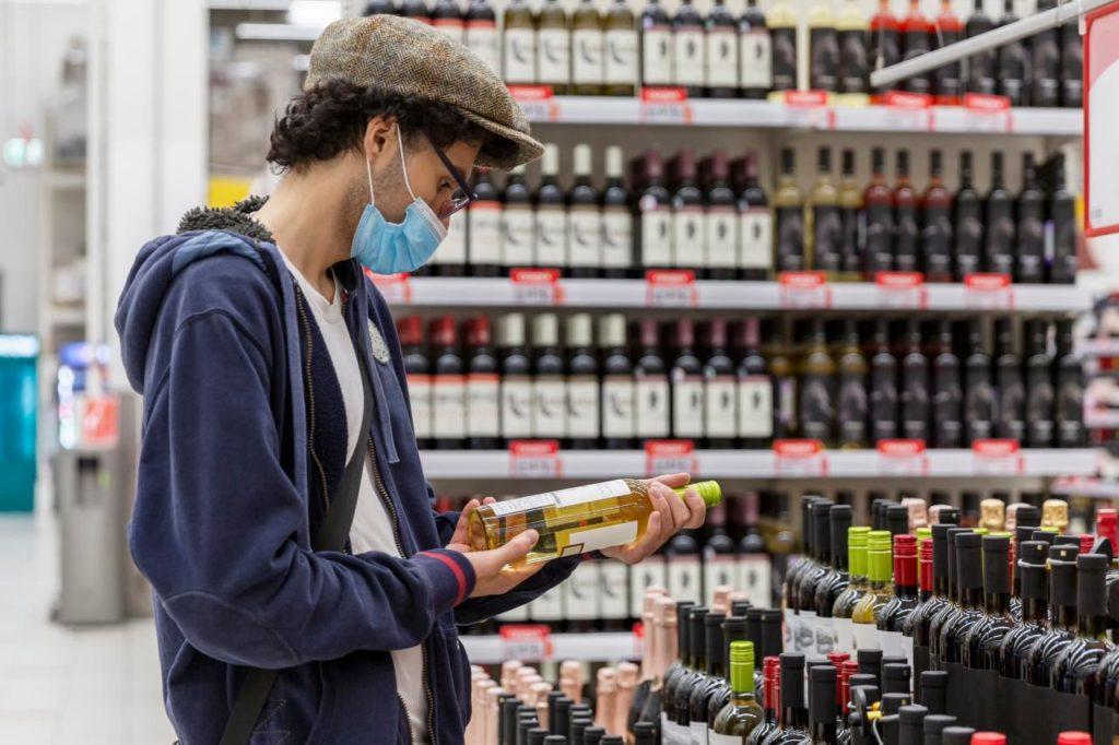 Un hombre compra vino en un comercio de alimentación
